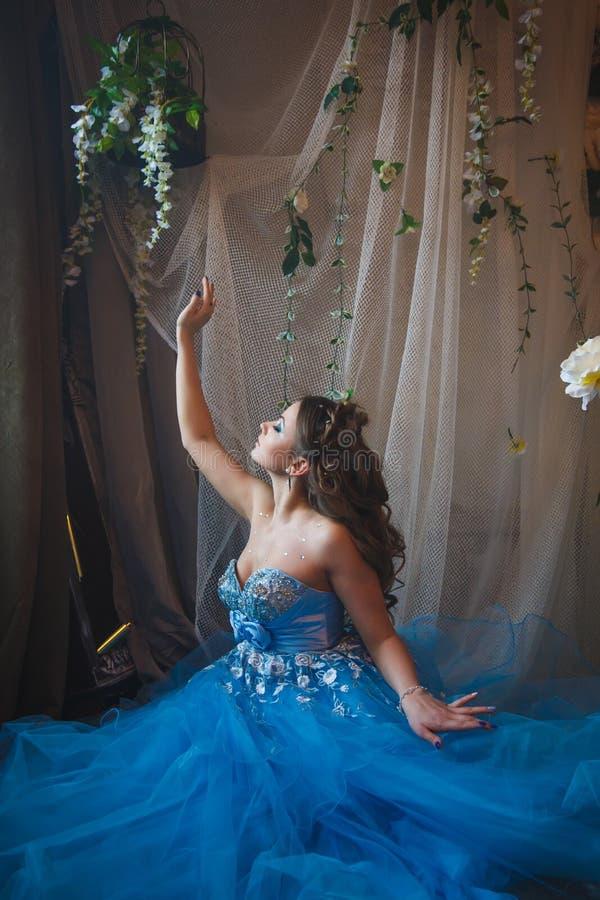 Jovem mulher bonita no vestido longo azul lindo como Cinderella com composição e penteado perfeitos fotos de stock royalty free