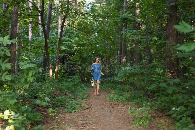 Jovem mulher bonita no vestido que corre na floresta do verão fotos de stock