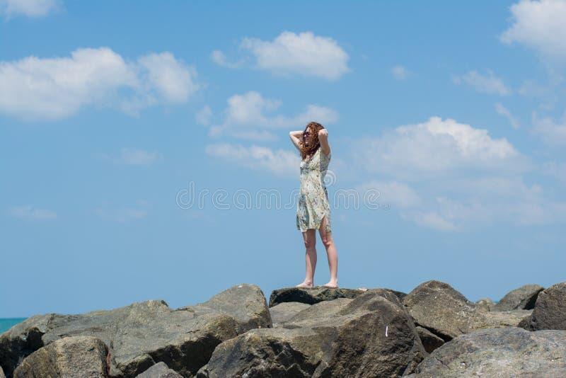 Jovem mulher bonita no vestido que está nas rochas imagem de stock