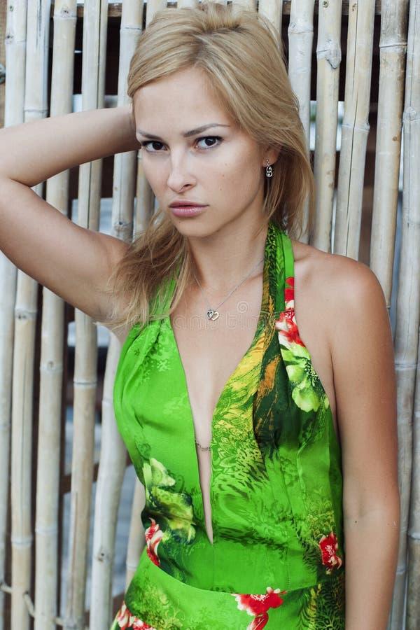Jovem mulher bonita no vestido verde agradável que levanta na parede de bambu branca Forme a foto, cabelo louro agradável, pele b fotos de stock