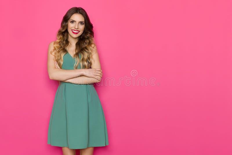 A jovem mulher bonita no vestido verde está levantando com os braços cruzados fotografia de stock