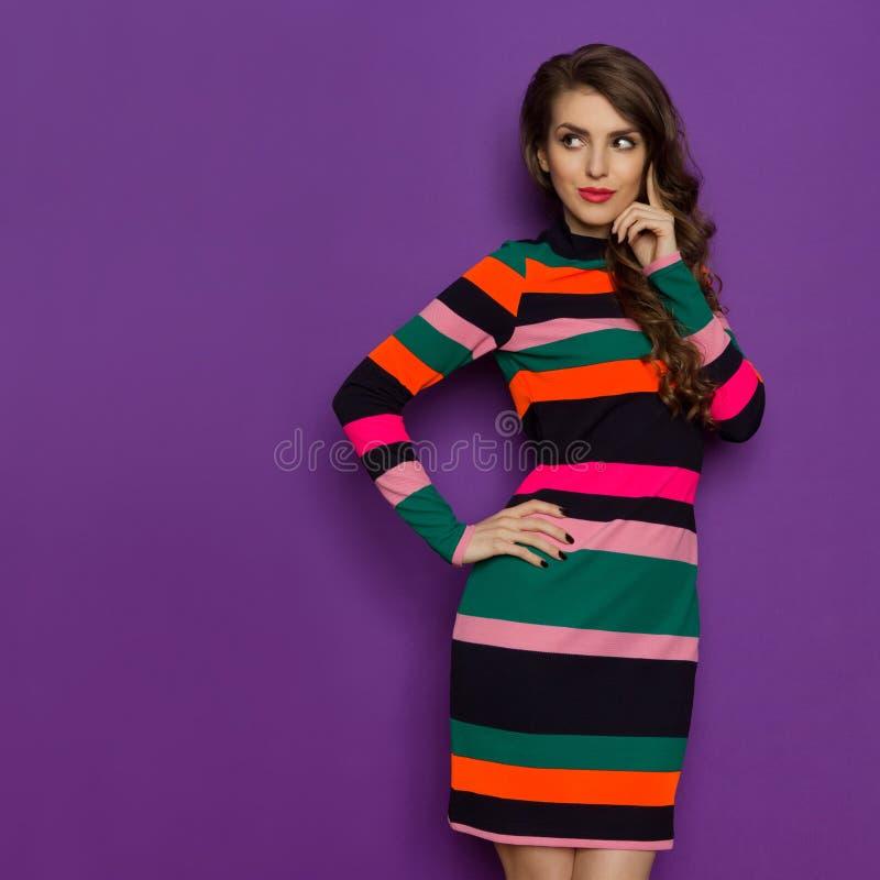 A jovem mulher bonita no vestido vibrante está olhando ausente e pensar foto de stock