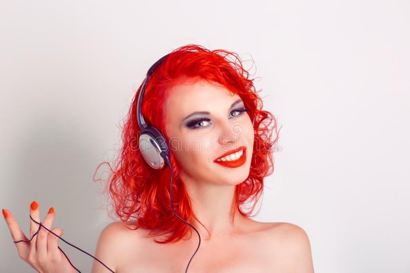 Jovem mulher bonita nos auscultadores que escuta a música imagens de stock royalty free