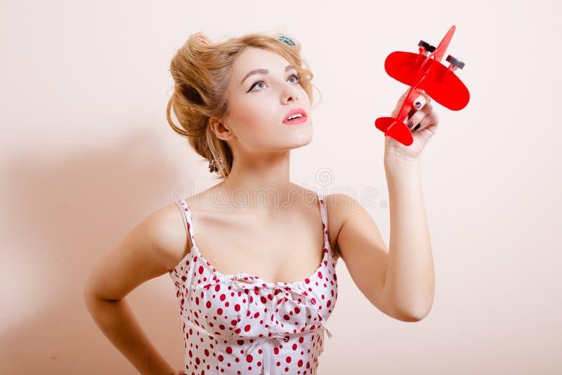 Jovem mulher bonita nos encrespadores grandes que guardam o brinquedo vermelho fotos de stock