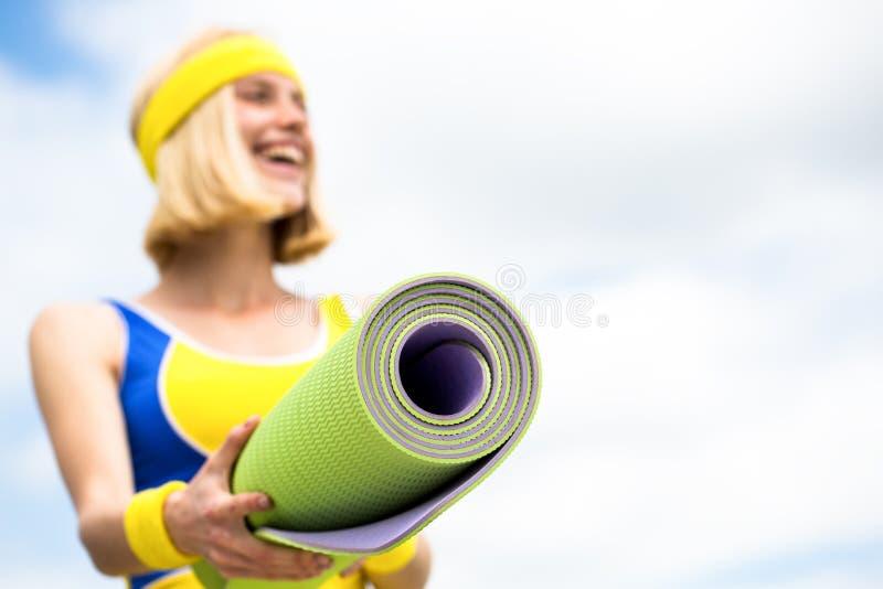 A jovem mulher bonita nos esportes veste está guardando uma esteira da ioga Forma, esporte, conceito saudável do estilo de vida M fotos de stock royalty free