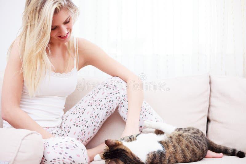 Jovem mulher bonita nos pijamas que jogam com seu gato em um sofá foto de stock royalty free