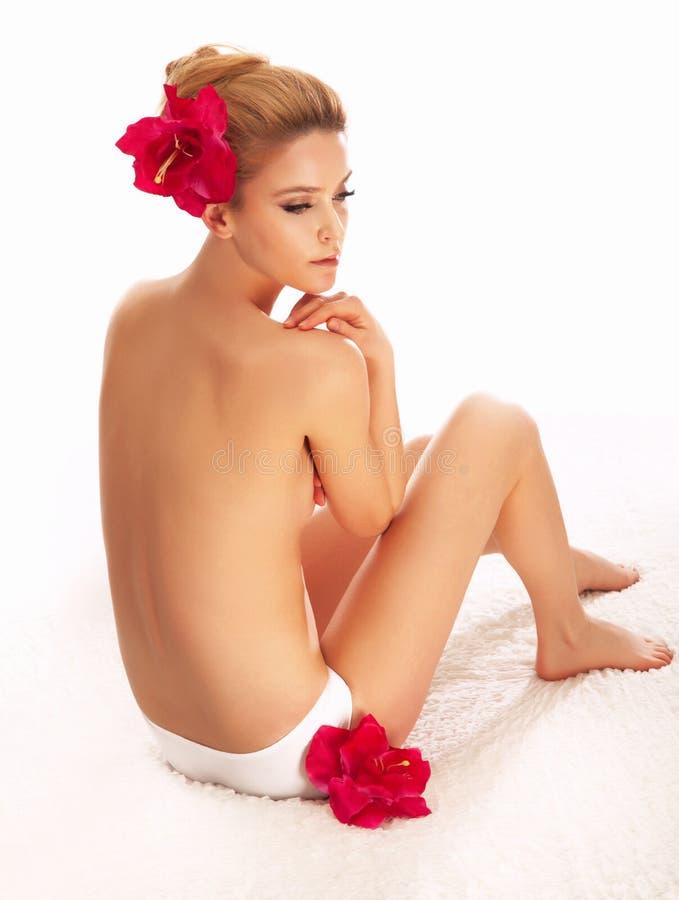 Mulher despida bonita nos termas com flores vermelhas. fotos de stock royalty free