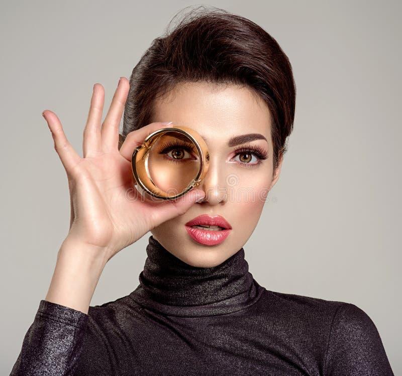 A jovem mulher bonita olha através do bracelete eyesight visão olhar fotos de stock