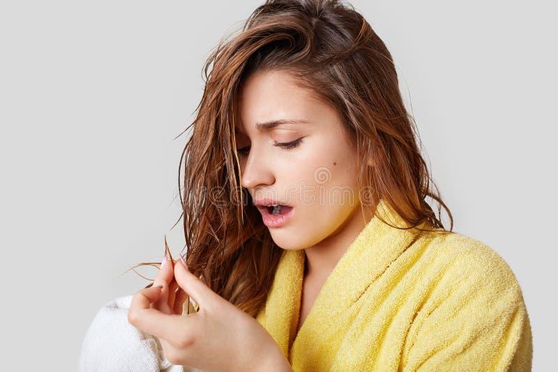 A jovem mulher bonita olha com descontentamento em seu cabelo danificado molhado, veste o roupão amarelo, precisa de mudar o cham foto de stock royalty free