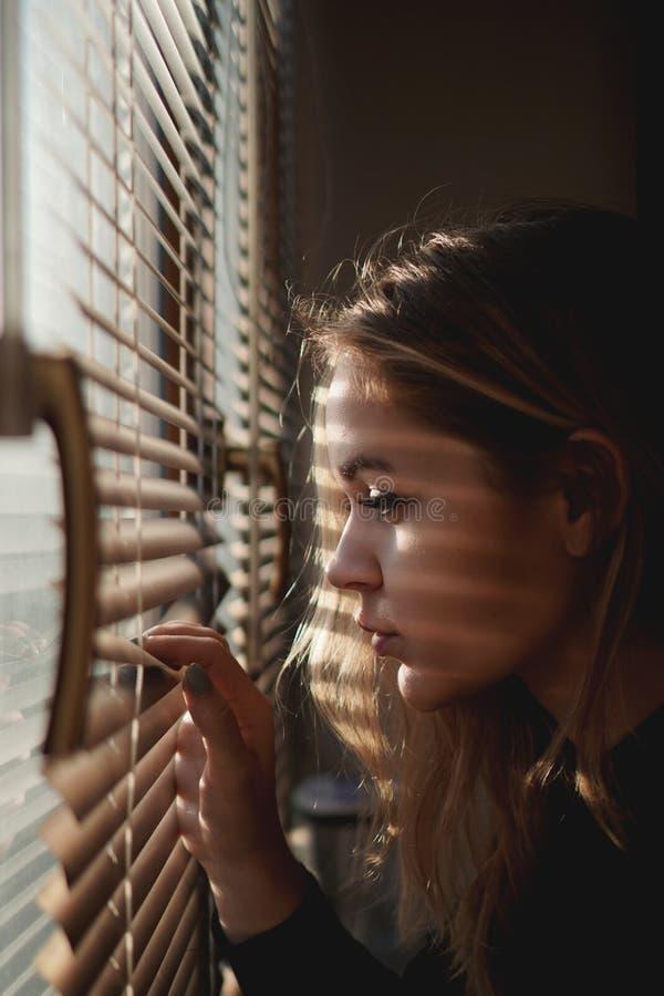 A jovem mulher bonita olha para fora através das cortinas foto de stock