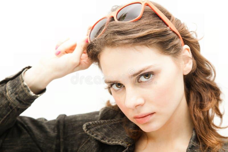 A jovem mulher bonita põe sobre óculos de sol imagens de stock