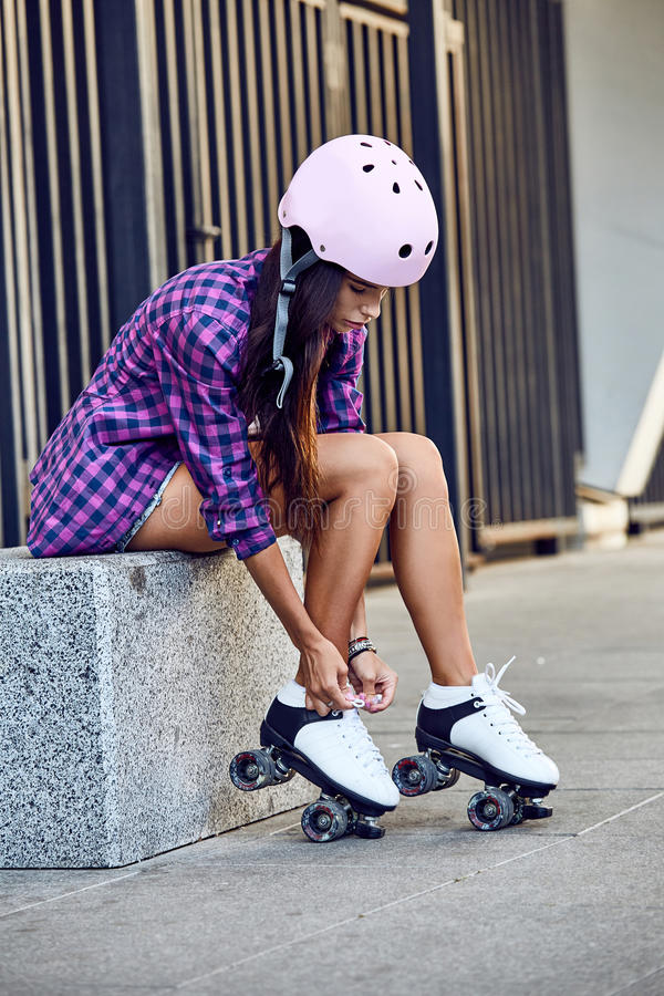 A jovem mulher bonita pôs sobre patins de rolo e laços da amarração fotografia de stock