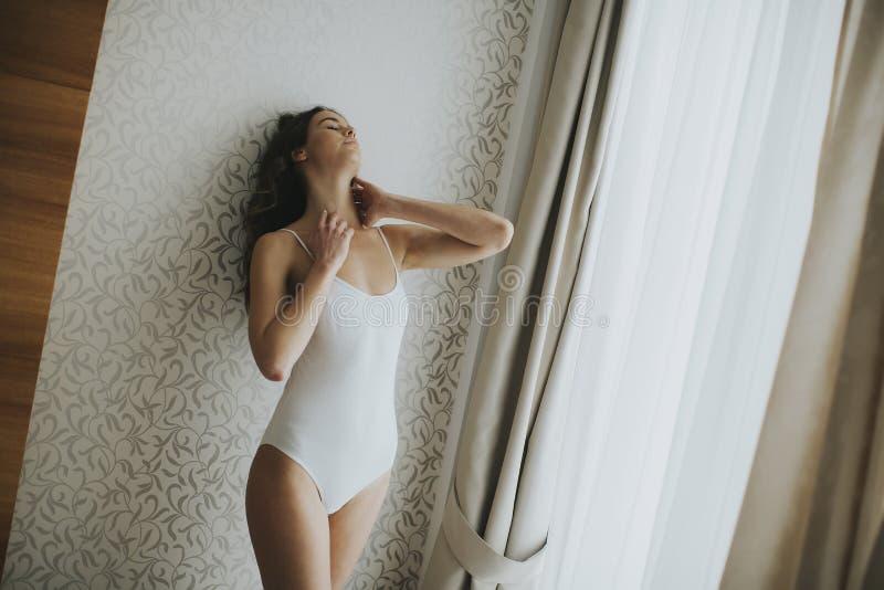 Jovem mulher bonita pela janela fotografia de stock