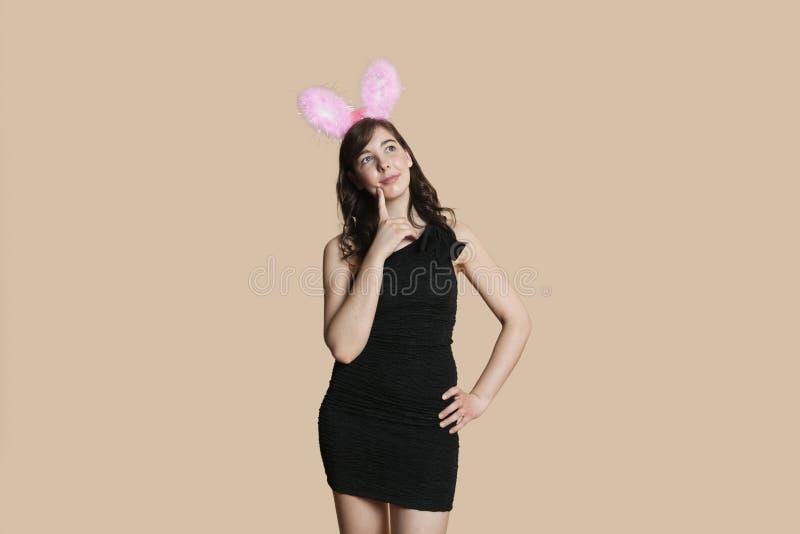 Jovem mulher bonita pensativa com as orelhas de coelho que olham afastado sobre o fundo colorido fotografia de stock royalty free