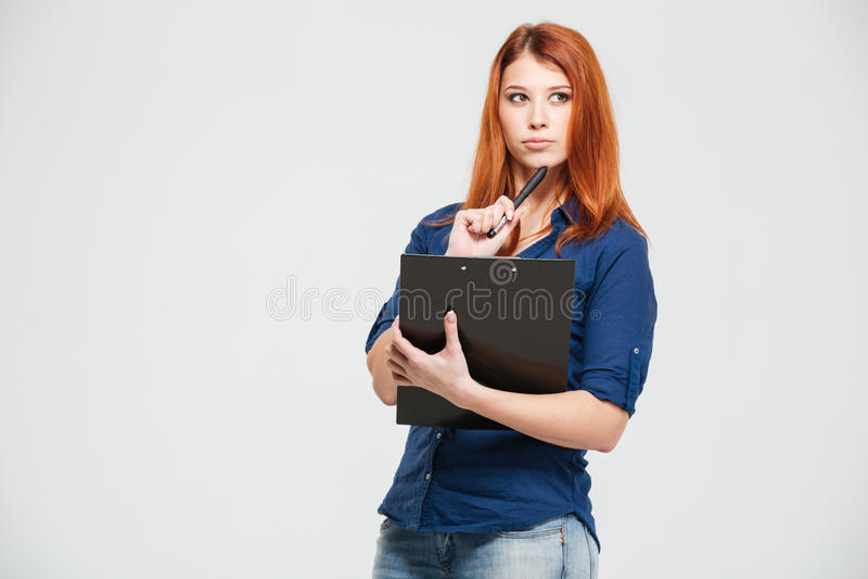 Jovem mulher bonita pensativa do ruivo que guarda a prancheta e o pensamento fotografia de stock royalty free