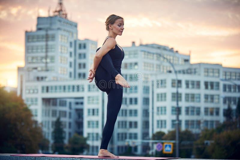 A jovem mulher bonita pratica o asana Utthita Hasta Padangushthasana da ioga - estando em uma pose do pé fora contra o backgroun imagens de stock