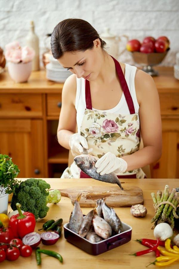 A jovem mulher bonita prepara peixes frescos em uma tabela completamente de vegetais orgânicos foto de stock