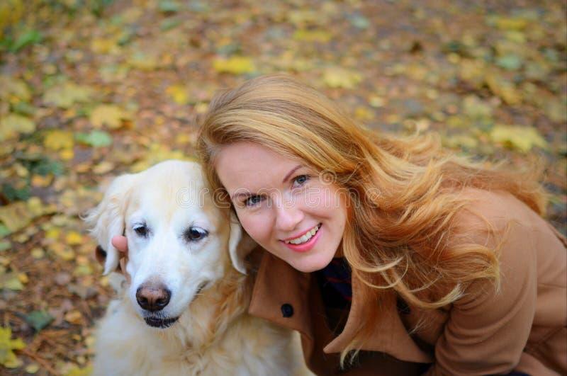 Jovem mulher bonita que anda com seu cão fotografia de stock royalty free