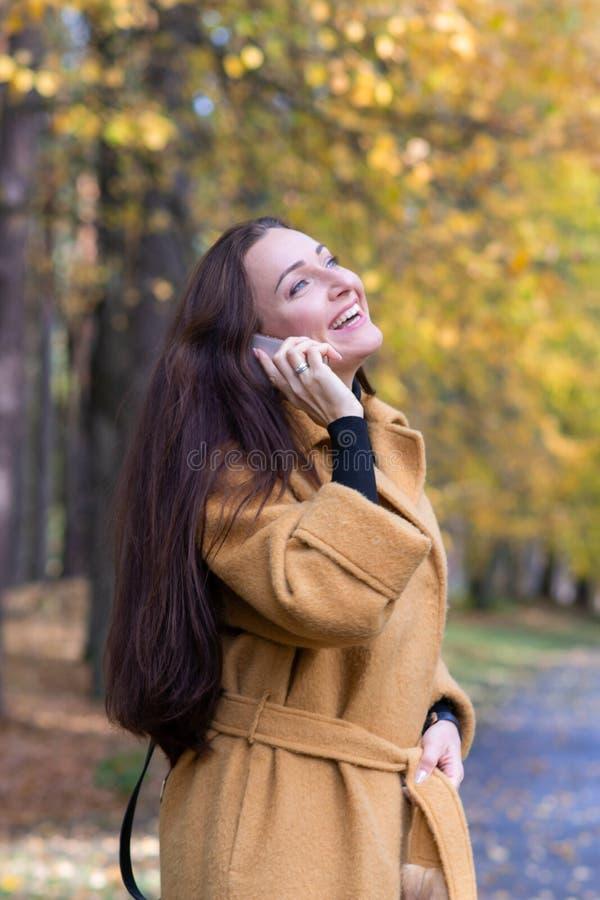 A jovem mulher bonita que anda em Autumn Park Talking na queda móvel das folhas do telefone relaxa imagens de stock royalty free