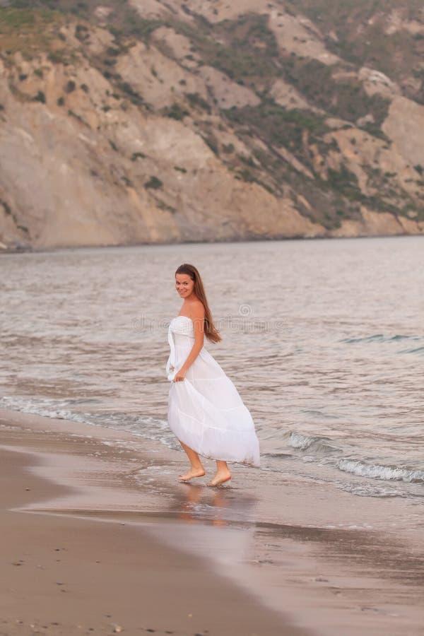 Jovem mulher bonita que anda em uma praia imagens de stock