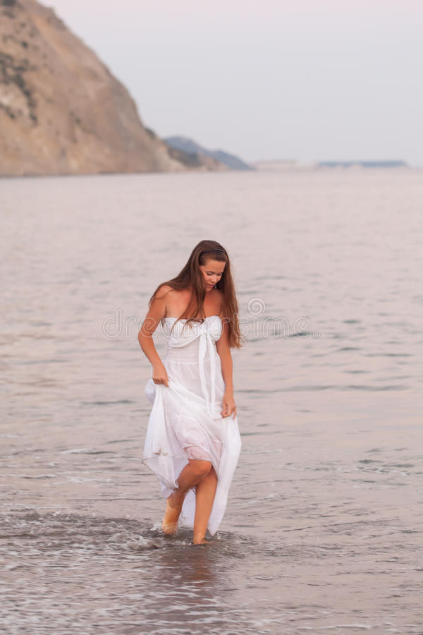 Jovem mulher bonita que anda em uma praia fotografia de stock
