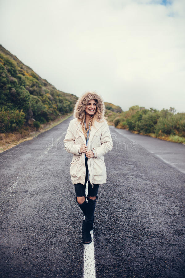 Jovem mulher bonita que anda na estrada vazia fotos de stock royalty free