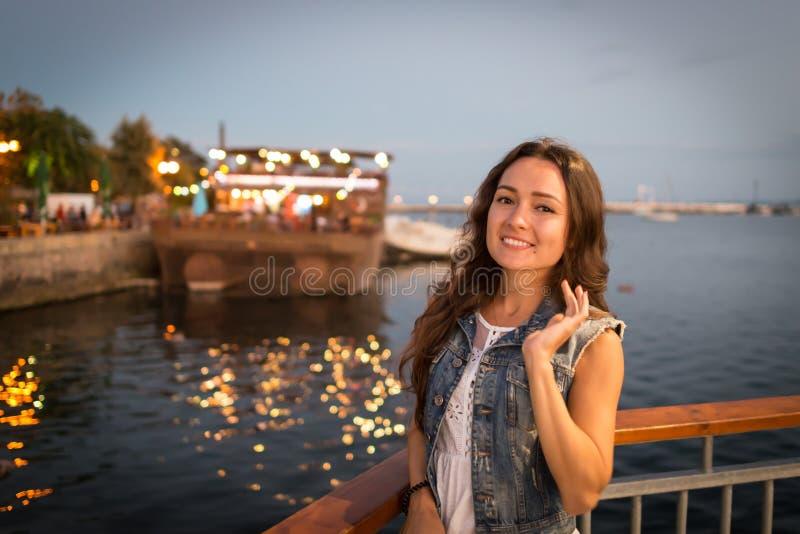Jovem mulher bonita que anda no passeio da cidade perto do mar na noite fotografia de stock royalty free