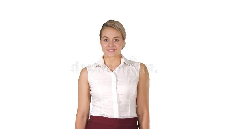Jovem mulher bonita que anda para a c?mera e que sorri no fundo branco fotografia de stock royalty free