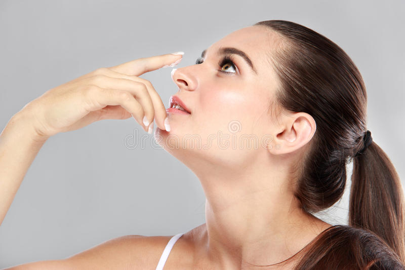 Jovem mulher bonita que aplica algum creme facial em seu nariz foto de stock royalty free