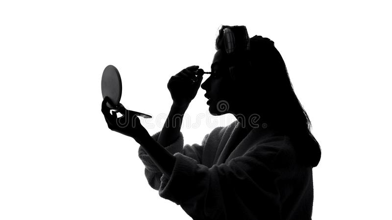 Jovem mulher bonita que aplica a composição na frente do espelho, conceito do rímel da beleza fotos de stock royalty free