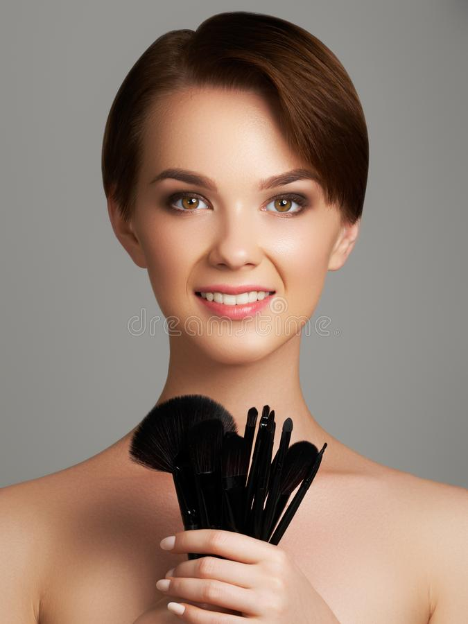 A jovem mulher bonita que aplica a fundação em sua cara com compõe a escova isolada no fundo cinzento imagens de stock