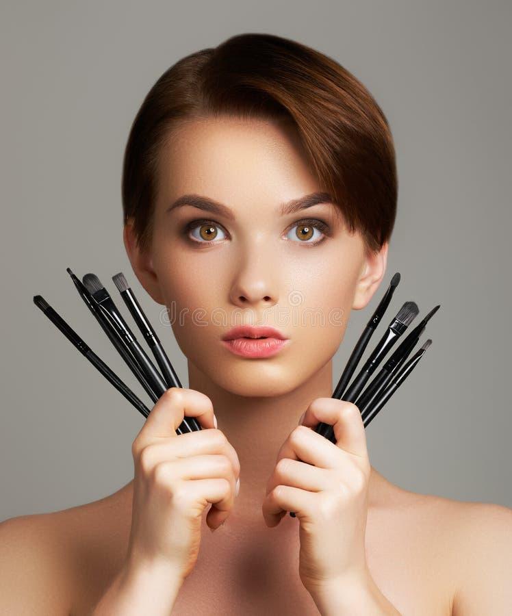 A jovem mulher bonita que aplica a fundação em sua cara com compõe a escova isolada no fundo cinzento fotos de stock royalty free