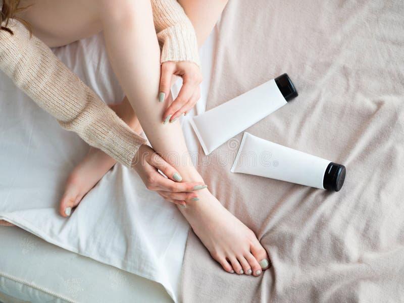 Jovem mulher bonita que aplica a loção do corpo na folha de cama Vista superior Etiqueta vazia para o modelo de marcagem com ferr imagens de stock