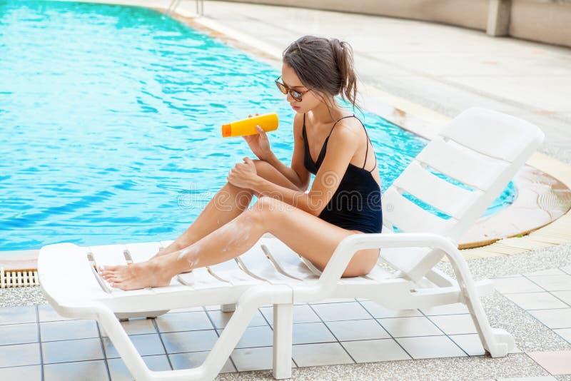 Jovem mulher bonita que aplica o creme do bloco do sol no pé Menina em b foto de stock royalty free