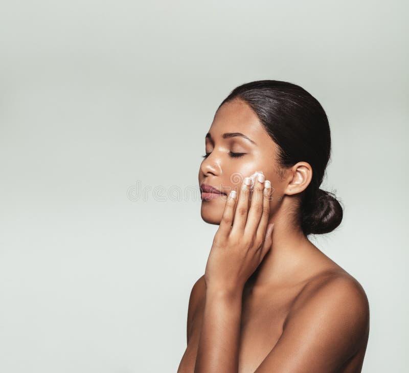 Jovem mulher bonita que aplica o creme hidratante a sua cara imagens de stock