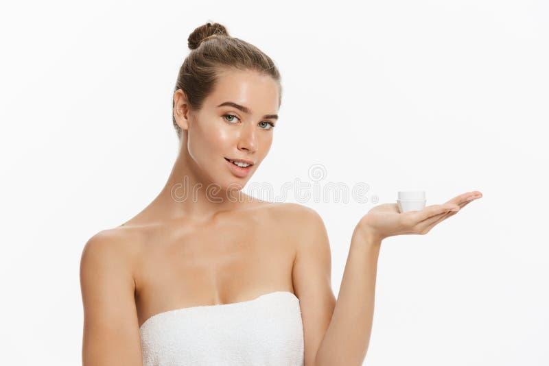 Jovem mulher bonita que aplica o tratamento de creme cosmético em sua cara isolada no fundo branco fotos de stock royalty free