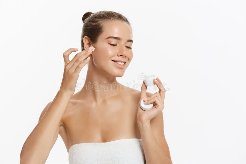 Jovem mulher bonita que aplica o tratamento de creme cosmético em sua cara isolada no fundo branco fotografia de stock royalty free
