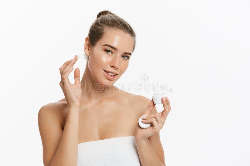 Jovem mulher bonita que aplica o tratamento de creme cosmético em sua cara isolada no fundo branco imagem de stock royalty free