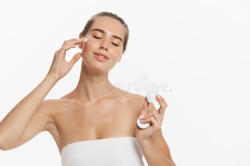 Jovem mulher bonita que aplica o tratamento de creme cosmético em sua cara isolada no fundo branco fotos de stock