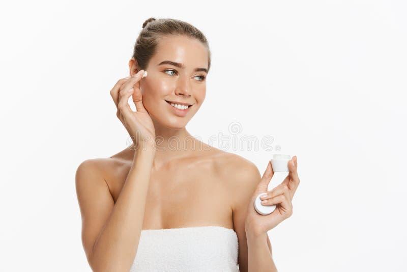 Jovem mulher bonita que aplica o tratamento de creme cosmético em sua cara isolada no fundo branco foto de stock royalty free