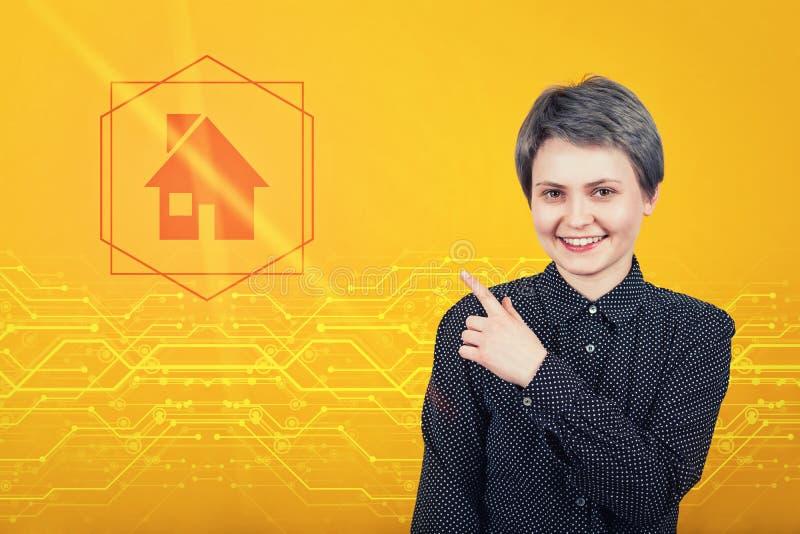 Jovem mulher bonita que aponta o dedo indicador afastado, mostrando à casa digital no ícone Tecnologia moderna, conceito do segur fotos de stock