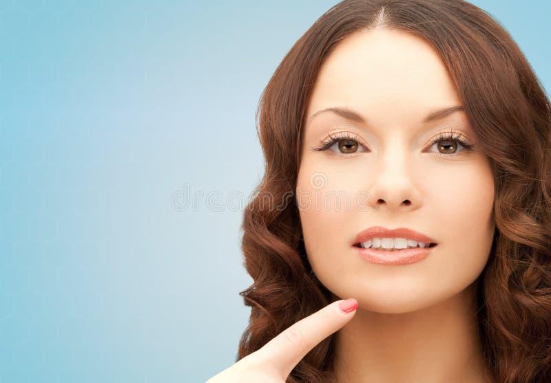 Jovem mulher bonita que aponta o dedo a seu queixo fotografia de stock