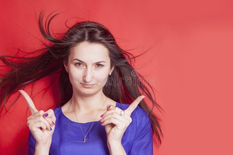 Jovem mulher bonita que aponta seu dedo para a área de espaço da cópia contra o fundo vermelho foto de stock