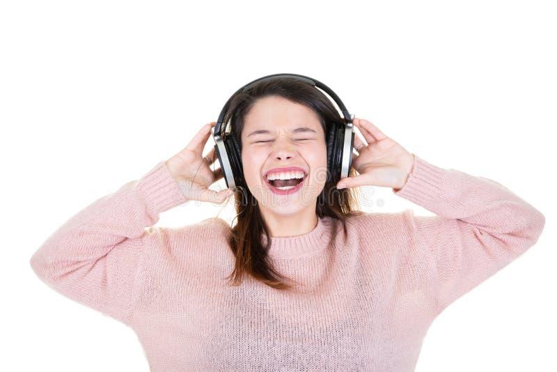 Jovem mulher bonita que aprecia e que dança no fundo branco que escuta a música por fones de ouvido sem fio foto de stock royalty free