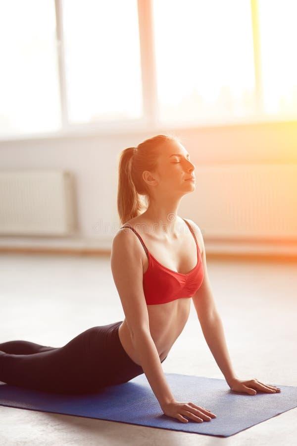 Jovem mulher bonita que aprecia a ioga dentro imagens de stock royalty free