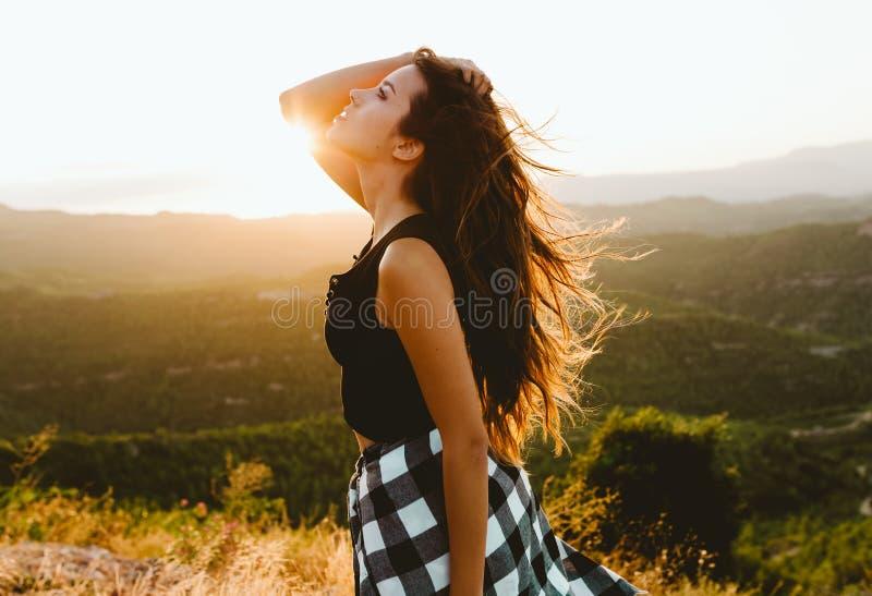 Jovem mulher bonita que aprecia a natureza no pico de montanha imagem de stock royalty free
