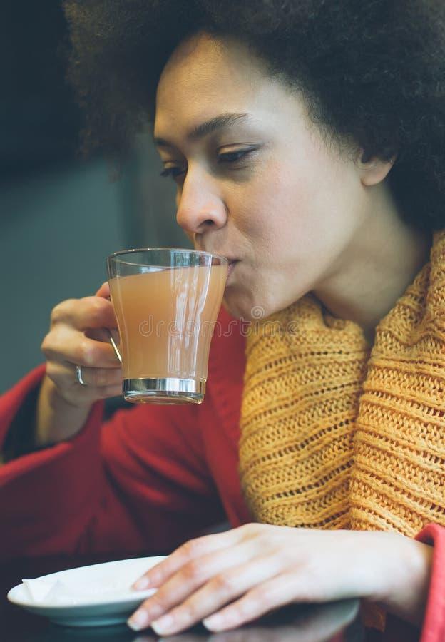 Jovem mulher bonita que aprecia o chá em um restaurante foto de stock royalty free