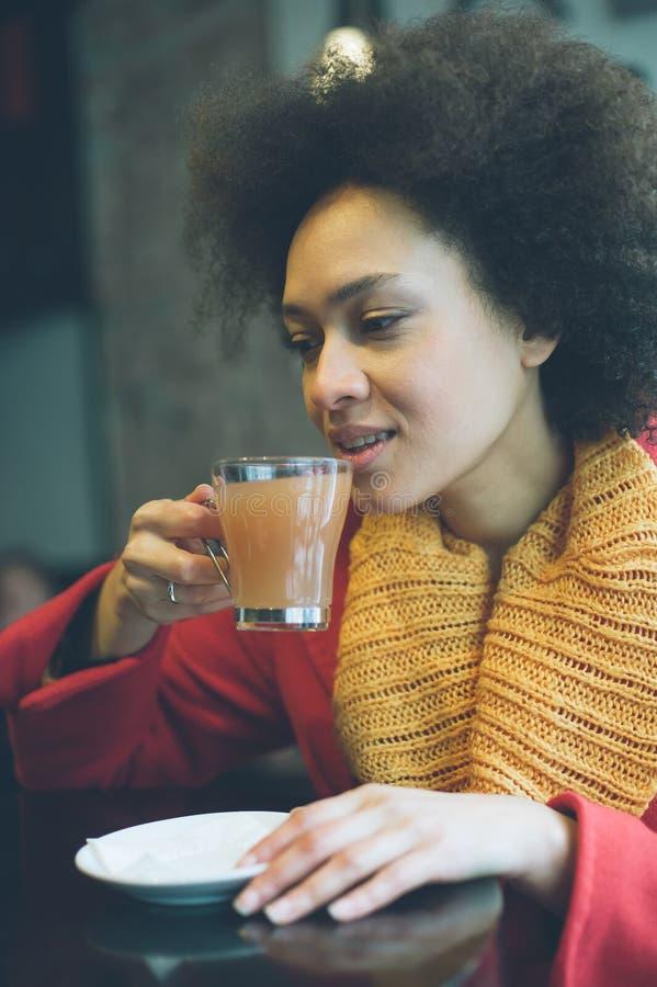 Jovem mulher bonita que aprecia o chá em um restaurante foto de stock