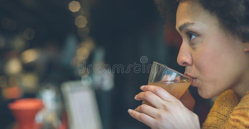 Jovem mulher bonita que aprecia o chá em um restaurante imagem de stock royalty free