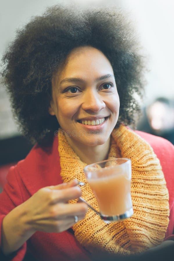 Jovem mulher bonita que aprecia o chá em um restaurante fotos de stock